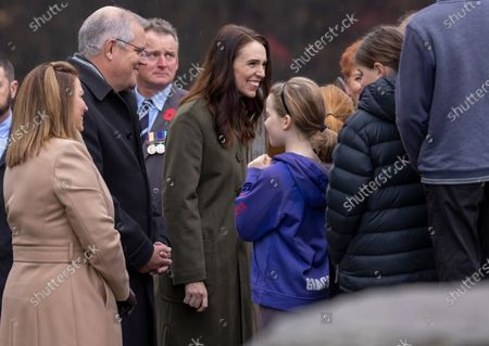 New Zealand Prime Minister Jacinda Ardern (C) and Australian Prime Minister Scott Morrison (2-R) meet members of the local school who sung the anthems during the wreath laying ceremony at the Arrowtown Cenotaph during the annual Australia-New Zealand Leaders' Meeting in Queenstown, New Zealand, 31 May 2021.