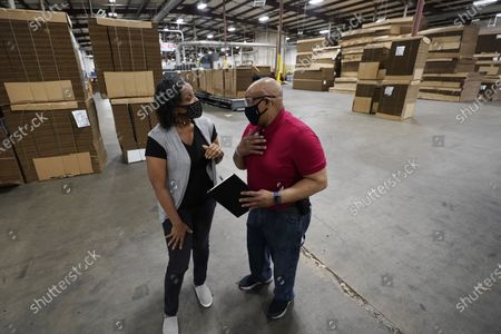 """Charita McCarrol, human resources manager at Great Southern Industries, a packaging company in Jackson, Miss., left, confers with second shift production manager James Chapman, . McCarrol said she has seen people abusing the $300-a-week federal supplement for people who lost their jobs during the COVID-19 pandemic, as well as other programs that offered extended support for the unemployed. """"You can't get people to come to work,"""" McCarrol said. """"It has been an absolute nightmare in the world of staffing agencies"""