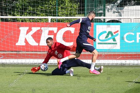 """French national soccer team, """"Les Bleus"""" goalkeeper Mike Maignan (background) wins his duel with French forward Karim Benzema during a training session in Clairefontaine-en-Yvelines"""