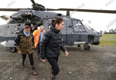 Stock Picture of New Zealand Prime Minister Jacinda Ardern, center, disembarks from an air force helicopter after flying over flood affected areas near Ashburton, south of Christchurch, New Zealand, . Floodwaters in New Zealand receded on Tuesday, leaving behind a big mess on many farms in the Canterbury region and damage to a major bridge