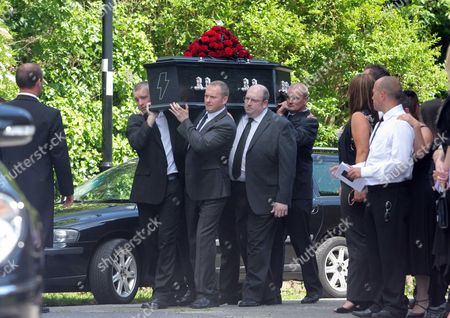 Pallbearers carry the coffin of Stuart Cable
