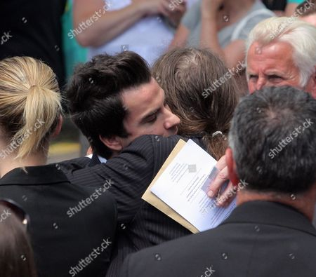 Kelly Jones of the Stereophonics (L) hugs a relative of Stuart Cable