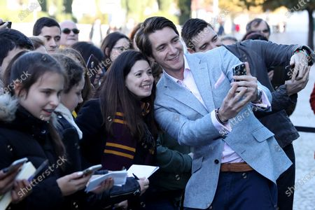 Stock Photo of Harry Potter's British actor James Phelps (R ) takes a selfie with fans during the opening of 'Harry Potter: The Exhibition' in Lisbon, Portugal, on November 16, 2019. Original props, costumes and film sets of the Harry Potter movies will be exhibited from November 16 to April 8, 2020 in Lisbon.
