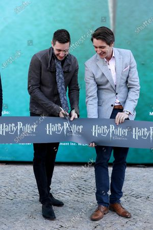 Harry Potter's British actors James Phelps (R) and Oliver Phelps (L) cut the ribbon during the opening of Harry Potter: The Exhibition in Lisbon, Portugal, on November 16, 2019. Original props, costumes and film sets of the Harry Potter movies will be exhibited from November 16 to April 8, 2020 in Lisbon.