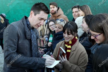 Harry Potter's British actor Oliver Phelps (L ) gives an autograph to fans during the opening of Harry Potter: The Exhibition in Lisbon, Portugal, on November 16, 2019. Original props, costumes and film sets of the Harry Potter movies will be exhibited from November 16 to April 8, 2020 in Lisbon.