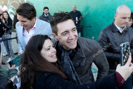 Harry Potter's British actor Oliver Phelps (R ) takes a selfie with fans during the opening of Harry Potter: The Exhibition in Lisbon, Portugal, on November 16, 2019. Original props, costumes and film sets of the Harry Potter movies will be exhibited from November 16 to April 8, 2020 in Lisbon.