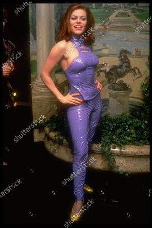 Member of pop group Deee-Lite, Lady Miss Kier posing backstage at Carlyle in purple vinyl catsuit & yellow pumps.