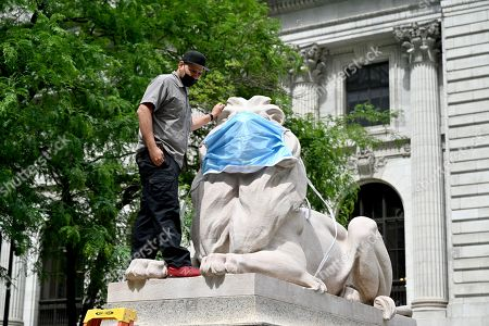Workers place a large face mask of the lion statues outside the New York Public Library Stephen A. Schwarzman Building in New York.