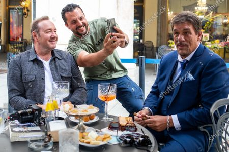 Kevin Spacey takes a selfie with a fan passing by their table, with Robert Davi in a cafe in downtown Turin