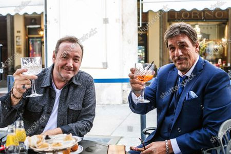 Stock Photo of Kevin Spacey and Robert Davi toast during their afternoon meeting in a cafe in downtown Turin