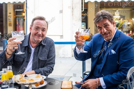 Kevin Spacey and Robert Davi toast during their afternoon meeting in a cafe in downtown Turin