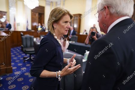 Sen. Shelley Moore Capito, R-W.Va., the leader of a group of Republican senators aiming to craft a deal with President Joe Biden on legislation focused on revamping the nation's physical infrastructure, confers with Sen. Roger Wicker, R-Miss., during a committee meeting at the Capitol in Washington. Biden and the West Virginia senator will meet Wednesday afternoon to work on their differences