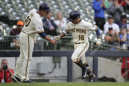 Milwaukee Brewers' Kolten Wong, right, is congratulated by third base coach Jason Lane, left, after hitting a solo home run during the first inning of a baseball game against the Detroit Tigers, in Milwaukee