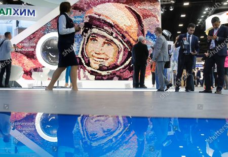 People walk past a portrait of the first cosmonaut Yuri Gagarin made by roses at the St. Petersburg International Economic Forum in St. Petersburg, Russia