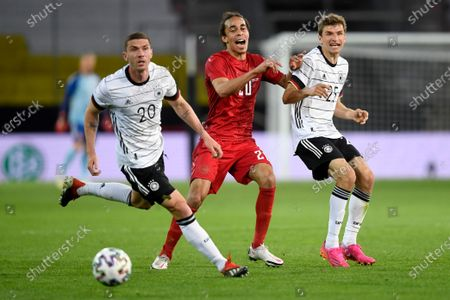 Denmark's Yussuf Yurary Poulsen reacts between Germany's Robin Gosens and Thomas Muller, right, during the international friendly soccer match between Germany and Denmark at the Tivoli Stadion Tirol in Innsbruck, Austria