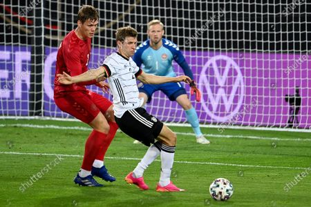 Stock Photo of Denmark's Jannik Vestergaard, left, vies for the ball with Germany's Thomas Muller during the international friendly soccer match between Germany and Denmark at the Tivoli Stadion Tirol in Innsbruck, Austria