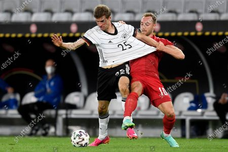 Stock Image of Denmark's Christian Eriksen pulls on the jersey of Germany's Thomas Muller during the international friendly soccer match between Germany and Denmark at the Tivoli Stadion Tirol in Innsbruck, Austria