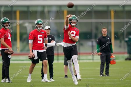 New York Jets backup quarterbacks James Morgan (4) and Mike White (5) watch quarterback Zach Wilson (2) throw a pass during an NFL football practice, in Florham Park, N.J
