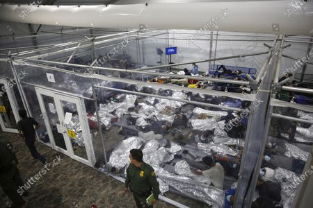 """Minors lie inside a pod at the Donna Department of Homeland Security holding facility, in Donna, Texas. A move by Texas Gov. Greg Abbott to shutter dozens of shelters housing about 4,000 migrant children is threatening to disrupt a national program offering care for minors who cross the U.S.-Mexico border. The U.S. Department of Health and Human Services said, that it didn't intend to close any facilities but that it was """"assessing"""" the Republican governor's late Tuesday disaster declaration"""