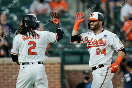 Baltimore Orioles' DJ Stewart (24) is greeted near home plate by Freddy Galvis (2) after Stewart scored both of them on a two-run home run against Minnesota Twins starting pitcher Randy Dobnak during the fifth inning of a baseball game, in Baltimore