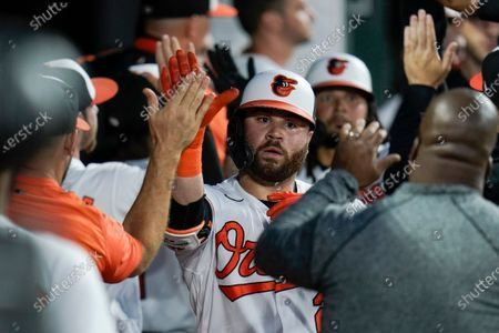 Baltimore Orioles' DJ Stewart, center, is greeted in the dugout after hitting a two-run home run off Minnesota Twins starting pitcher Randy Dobnak during the fifth inning of a baseball game, in Baltimore. Orioles' Freddy Galvis scored on the home run