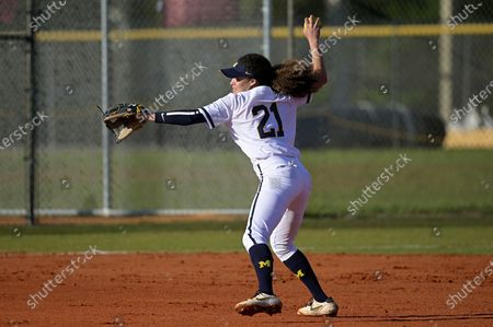 Michigan infielder Natalia Rodriguez (21) throws while warming up during an NCAA college softball game against Wisconsin, in Leesburg, Fla