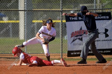 Wisconsin's Peyton Bannon slides safely into third base under Michigan infielder Natalia Rodriguez (21) during an NCAA college softball game, in Leesburg, Fla