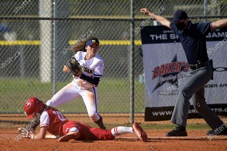 Wisconsin's Peyton Bannon (22) slides safely into third base under Michigan infielder Natalia Rodriguez (21) during an NCAA college softball game, in Leesburg, Fla