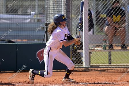 Michigan's Natalia Rodriguez (21) watches after hitting a pitch during an NCAA college softball game against Wisconsin, in Leesburg, Fla