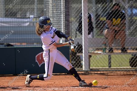 Michigan's Natalia Rodriguez (21) hits a pitch during an NCAA college softball game against Wisconsin, in Leesburg, Fla