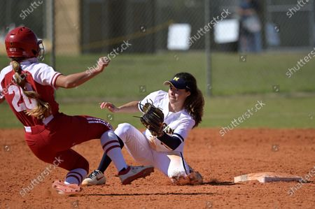 Michigan infielder Natalia Rodriguez, right, tags out Wisconsin's Gabby Altobelli (28) at second base during an NCAA college softball game, in Leesburg, Fla
