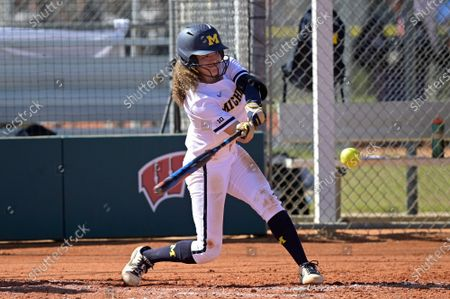 Michigan infielder Natalia Rodriguez (21) hits a pitch during an NCAA college softball game against Wisconsin, in Leesburg, Fla