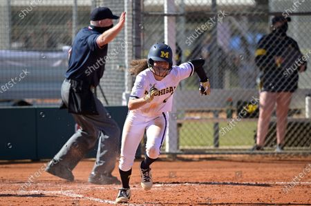 Michigan infielder Natalia Rodriguez (21) runs to first base after hitting a pitch during an NCAA college softball game against Wisconsin, in Leesburg, Fla
