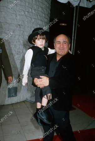 Actor Danny DeVito holding actor Miko Hughes.