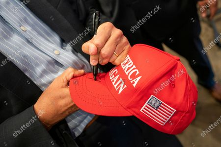 Michael Flynn, former national security adviser to former President Donald Trump, signs a MAGA hat as he greets attendees at the end of a campaign event where he endorsed New York City mayoral candidate Fernando Mateo, in Staten Island, N.Y