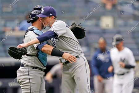 Stock Photo of Tampa Bay Rays catcher Mike Zunino, left, congratulates Rays starting pitcher Ryan Yarbrough, center, with an embrace after Yarbrough pitched a complete baseball game in the Rays 9-2 victory over the New York Yankees, at Yankee Stadium in New York