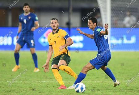 Kuwait's Fawaz Alotaibi, right, is challenged by Australia's Mathew Leckie during the World Cup 2022 Group B qualifying soccer match between Kuwait and Australia in Kuwait City, Kuwait