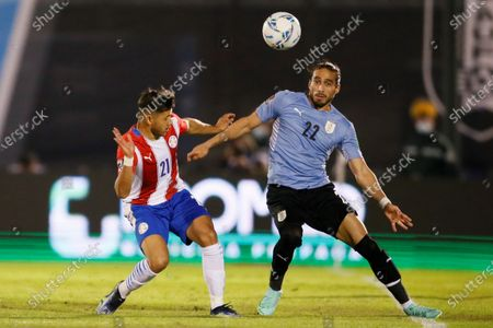 Martin Caceres (R) of Uruguay vies for the ball with Oscar Romero of Paraguay during the South American Qualifying for the Qatar 2022 World Cup soccer match between Uruguay and Paraguay at Centenario stadium in Montevideo, Uruguay, 03 June 2021.