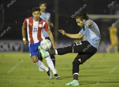 Uruguay's Martin Caceres clears a ball as Paraguay's Oscar Romero looks on during a World Cup qualifying soccer match in Montevideo, Uruguay