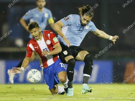 Uruguay's Martin Caceres, left, and Paraguay's Oscar Romero fight for the ball during a World Cup qualifying soccer match in Montevideo, Uruguay
