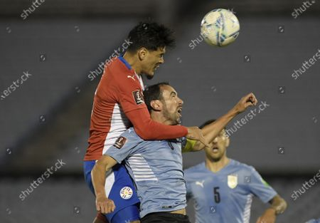 Paraguay's Gustavo Gomez, top, and Uruguay's Diego Godin battle for the ball during a World Cup qualifying soccer match in Montevideo, Uruguay