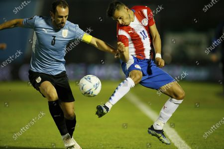 Stock Photo of Uruguay's Diego Godin, left, and Paraguay's Angel Romero battle for the ball during a World Cup qualifying soccer match in Montevideo, Uruguay