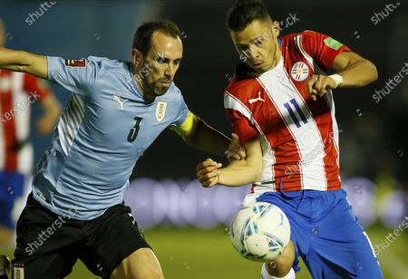 Uruguay's Diego Godin, left, and Paraguay's Angel Romero battle for the ball during a World Cup qualifying soccer match in Montevideo, Uruguay