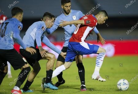 Stock Photo of Paraguay's Miguel Almiron, right, controls the ball ahead of Uruguay's Jose Maria Gimenez, left, and Rodrigo Bentancur, behind, during a World Cup qualifying soccer match in Montevideo, Uruguay