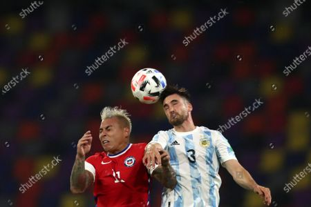 Chile's Eduardo Vargas, left, and Argentina's Nicolas Tagliafico go for a header during a qualifying soccer match for the FIFA World Cup Qatar 2022 in Santiago del Estero, Argentina