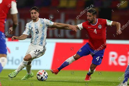 Chile's Mauricio Isla, right, and Argentina's Nicolas Tagliafico battle for the ball during a qualifying soccer match for the FIFA World Cup Qatar 2022 in Santiago del Estero, Argentina