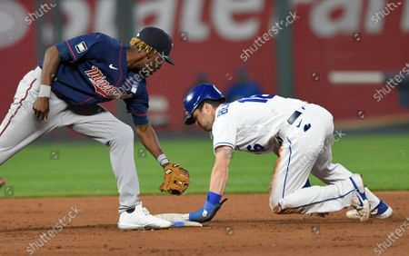 Kansas City Royals' Whit Merrifield steals second base next to Minnesota Twins second baseman Nick Gordon during the fifth inning of a baseball game, in Kansas City, Mo