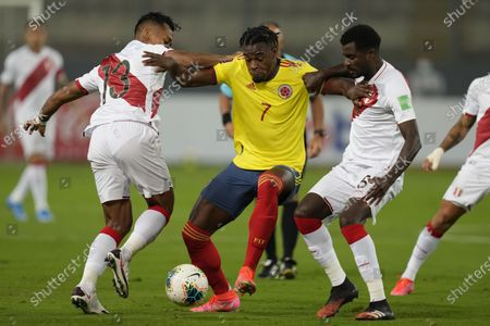 Stock Photo of Colombia's Duvan Zapata battles, center, battles with Peru's Renato Tapia, left, and Peru's Miguel Araujo during a qualifying soccer match for the FIFA World Cup Qatar 2022 at the National stadium in Lima, Peru