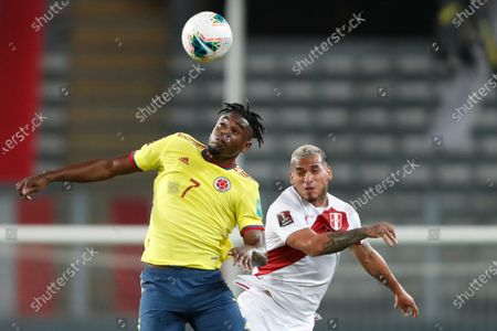 Colombia's Duvan Zapata and Peru's Miguel Trauco go for a header during a qualifying soccer match for the FIFA World Cup Qatar 2022 at the National stadium in Lima, Peru