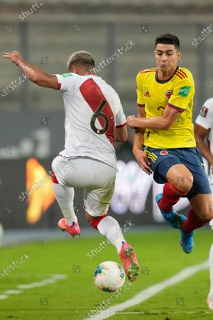 Colombia's Stefan Medina, left, and Peru's Miguel Trauco battle for the ball during a qualifying soccer match for the FIFA World Cup Qatar 2022 at the National stadium in Lima, Peru